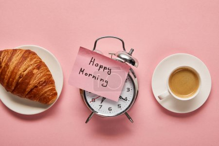 top view of alarm clock with happy morning lettering on sticky note near coffee and croissant on pink background