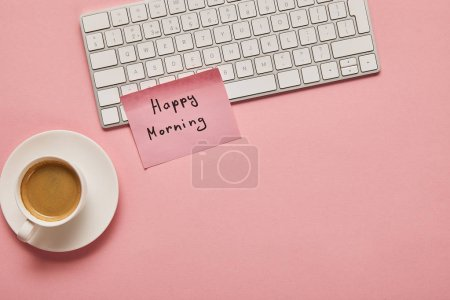 top view of computer keyboard and pink sticky note with happy morning lettering near coffee on pink background