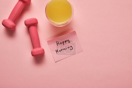 Photo for Top view of orange juice, pink dumbbells and sticky note with happy morning lettering on pink background - Royalty Free Image