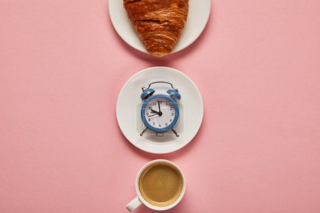 Photo for Flat lay with coffee cup, toy alarm clock and croissant on plate on pink background - Royalty Free Image