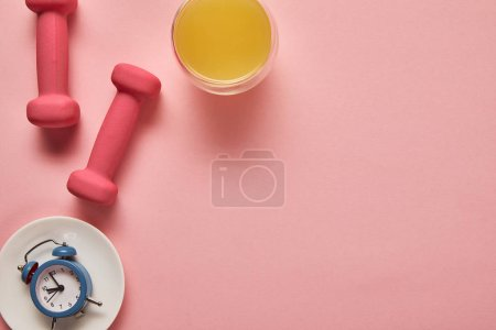 Photo for Top view of orange juice, pink dumbbells and toy alarm clock on plate on pink background - Royalty Free Image