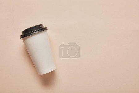 Photo pour Vue du dessus de la tasse en papier avec espace de copie sur fond beige - image libre de droit