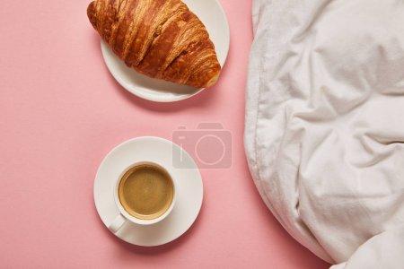 Foto de Vista superior de la manta, el café y el cruasán sobre fondo rosa - Imagen libre de derechos