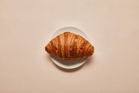 Photo for Top view of tasty croissant on white plate on beige background - Royalty Free Image