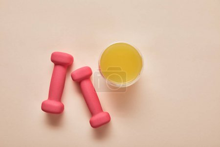 Photo for Top view of pink dumbbells, orange juice on beige background - Royalty Free Image
