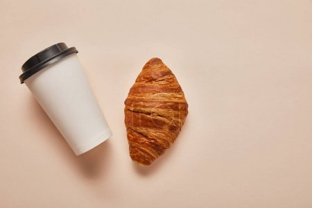 Photo for Top view of coffee to go and tasty croissant on beige background - Royalty Free Image