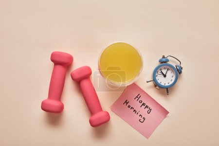 Foto de Top view of sticky note with happy morning lettering, pink dumbbells, orange juice and small alarm clock on beige background - Imagen libre de derechos