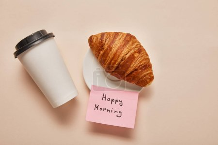 Photo for Top view of coffee to go, croissant and sticky note with happy morning lettering on beige background - Royalty Free Image