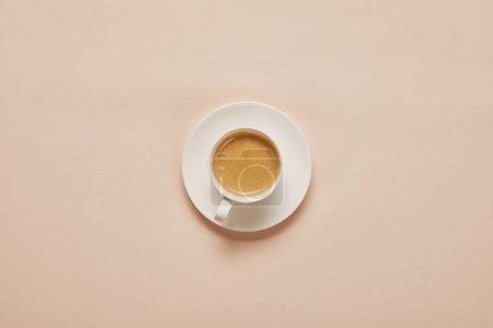 Photo pour Vue du haut du café en tasse sur soucoupe sur fond beige - image libre de droit