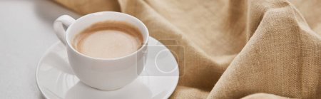 Photo for Close up view of coffee in white cup on saucer near beige napkin, panoramic shot - Royalty Free Image