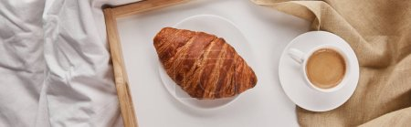 Photo for Top view of fresh croissant with coffee on wooden tray in bed at morning, panoramic shot - Royalty Free Image
