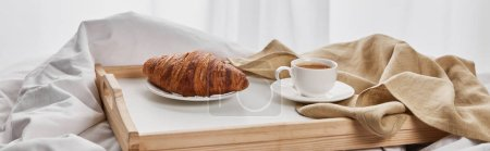 Photo for Coffee and croissant served on wooden tray on white bedding, panoramic shot - Royalty Free Image