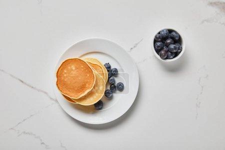 Foto de Vista superior de los panqueques en el plato cerca de un tazón con arándanos en la superficie texturizada - Imagen libre de derechos