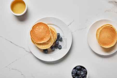 Photo for Top view of plates with pancakes and two bowls with honey and blueberries - Royalty Free Image