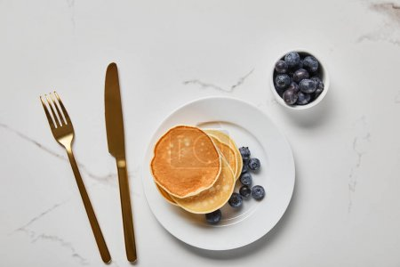 Photo for Top view of pancakes on plate near golden cutlery and bowl with blueberries - Royalty Free Image