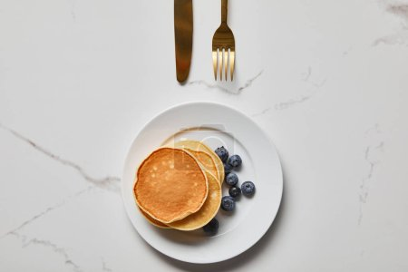 Photo for Top view of pancakes with blueberries on plate near golden fork and knife - Royalty Free Image