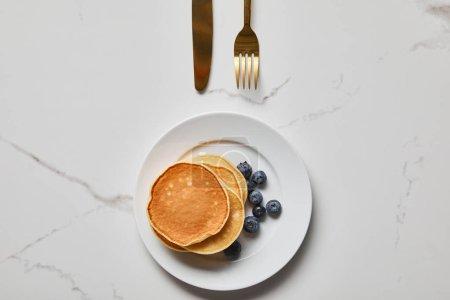 Foto de Vista superior de panqueques con arándanos en el plato cerca de tenedor dorado y cuchillo - Imagen libre de derechos