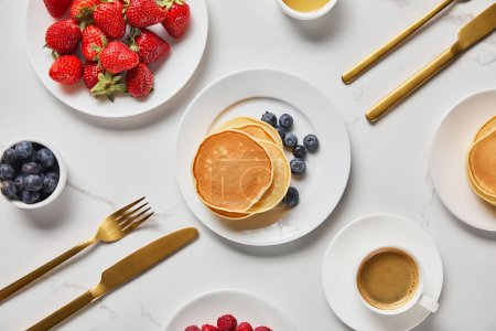 Photo for Top view of served breakfast with berries, pancakes and cup of coffee - Royalty Free Image