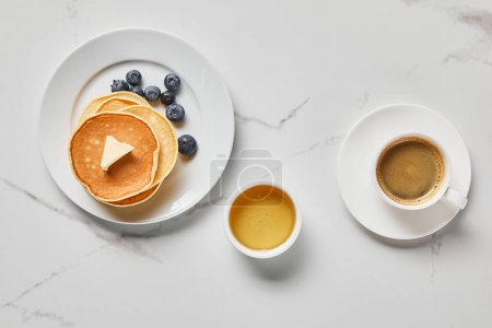 Photo for Top view of bowl with honey, tasty pancakes with blueberries and cup of coffee - Royalty Free Image