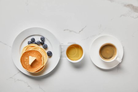 Photo for Top view of bowl with honey, tasty pancakes with blueberries and butter, and cup of coffee - Royalty Free Image