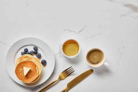 Photo for Top view of bowl with honey, tasty pancakes with blueberries and cup of coffee near golden cutlery - Royalty Free Image