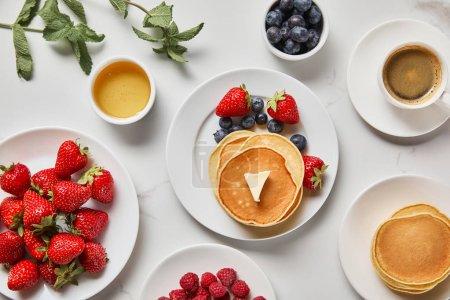 Photo pour Vue de dessus du petit déjeuner sain avec fraises, bleuets, framboises, crêpes, miel et tasse de café - image libre de droit