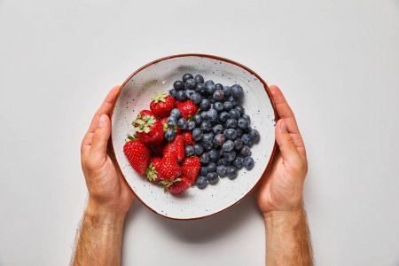Photo for Cropped view of man holding big plate with tasty strawberries and blue berries - Royalty Free Image