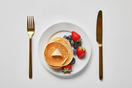 Photo for Top view of strawberries, blueberries and pancakes on plate near golden fork and knife - Royalty Free Image