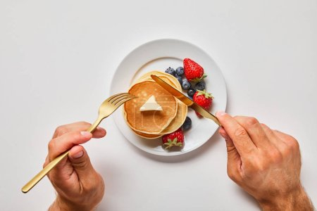 Photo for Cropped view of man cutting pancakes on plate with blueberries and strawberries - Royalty Free Image