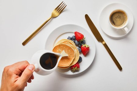 Photo for Cropped view of man pouring syrup on pancakes with berries near golden cutlery and cup of coffee - Royalty Free Image