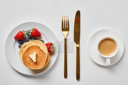 Photo for Top view of tasty breakfast with pancakes, berries and cup of coffee near golden cutlery - Royalty Free Image