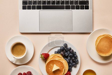 Photo for Top view of tasty breakfast with pancakes, berries, cup of coffee and honey near laptop - Royalty Free Image