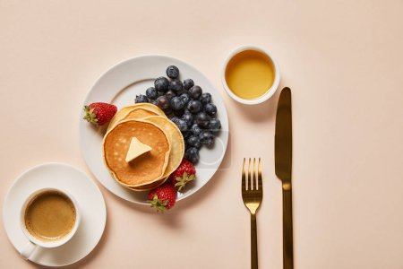 Photo for Top view of breakfast with cup of coffee, pancakes, strawberries, blueberries and honey near golden cutlery - Royalty Free Image
