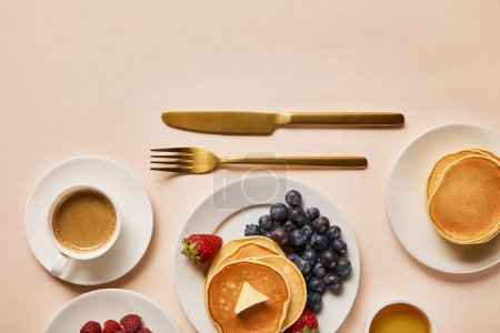 Photo for Top view of tasty served breakfast with pancakes, berries, honey and coffee near golden cutlery - Royalty Free Image