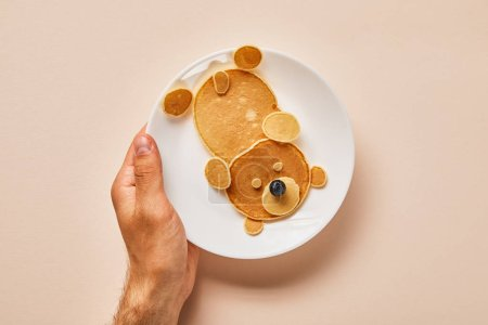Photo for Cropped view of pancakes on plate with one blueberry on pink, bear concept - Royalty Free Image