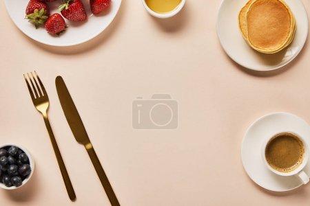 Foto de Vista superior del desayuno servido con bayas, café, tortitas y espacio vacío en el medio - Imagen libre de derechos