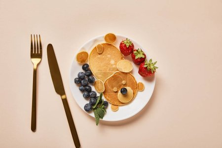 Photo for Top view of pancakes, blueberries and strawberries on plate near golden cutlery, bear concept - Royalty Free Image