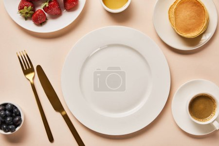 Photo for Top view of served breakfast with berries, coffee, pancakes and empty plate in middle on pink background - Royalty Free Image