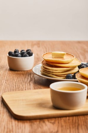 Photo for Selective focus of pancakes with butter, blueberries and honey on wooden surface isolated on grey - Royalty Free Image