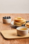 """Постер, картина, фотообои """"selective focus of pancakes with butter, blueberries and honey on wooden surface isolated on grey """""""
