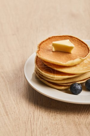 Photo for Pancakes with butter and blueberries on plate on wooden surface - Royalty Free Image