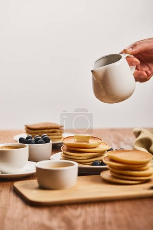 Photo for Cropped view of man holding jug with syrup upon plate with pancakes and blueberries near cup of coffee and bowl with honey isolated on grey - Royalty Free Image