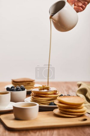 Photo for Cropped view of man pouring tasty pancakes with syrup from jug near bowls with blueberries and honey, and cup of coffee isolated on grey - Royalty Free Image