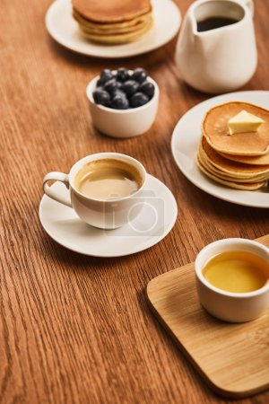 Photo for Selective focus of cup of coffee on saucer near plate with pancakes and bowls with honey and blueberries on wooden surface - Royalty Free Image