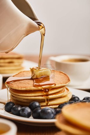 Photo pour Mise au point sélective du sirop versant sur les crêpes avec du beurre et des bleuets près de tasse de café - image libre de droit