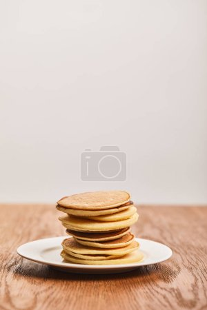 Photo for Tasty pancakes for breakfast on white plate on wooden surface isolated on grey - Royalty Free Image