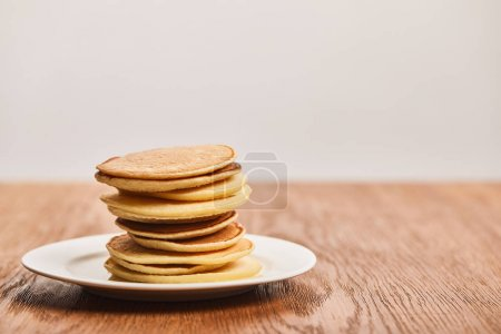 Foto de Many tasty pancakes on white plate on wooden surface isolated on grey - Imagen libre de derechos