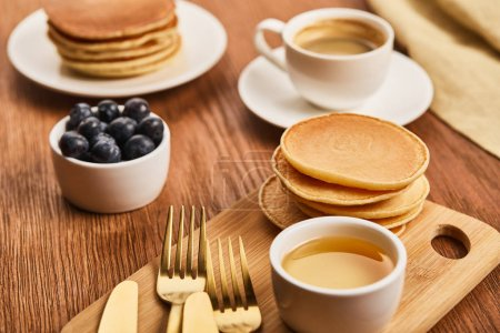 Photo for Selective focus of pancakes near bowl with honey and blueberries, golden cutlery and cup of coffee - Royalty Free Image