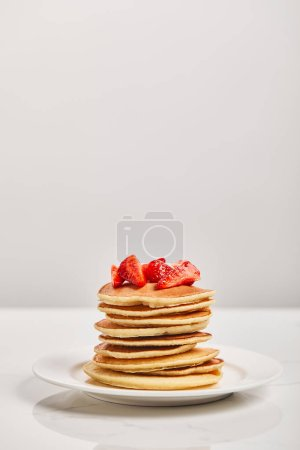 Photo for Pancakes for breakfast with strawberries on white plate isolated on grey - Royalty Free Image