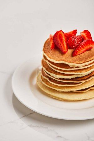Photo for Tasty pancakes with strawberries on white plate on textured surface - Royalty Free Image